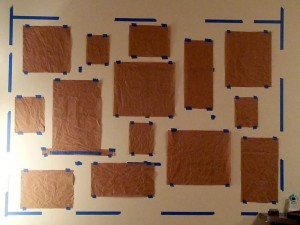 Laying out photo wall with 3x3 grid marked with painters tape and using brown paper templates for frame positioning.
